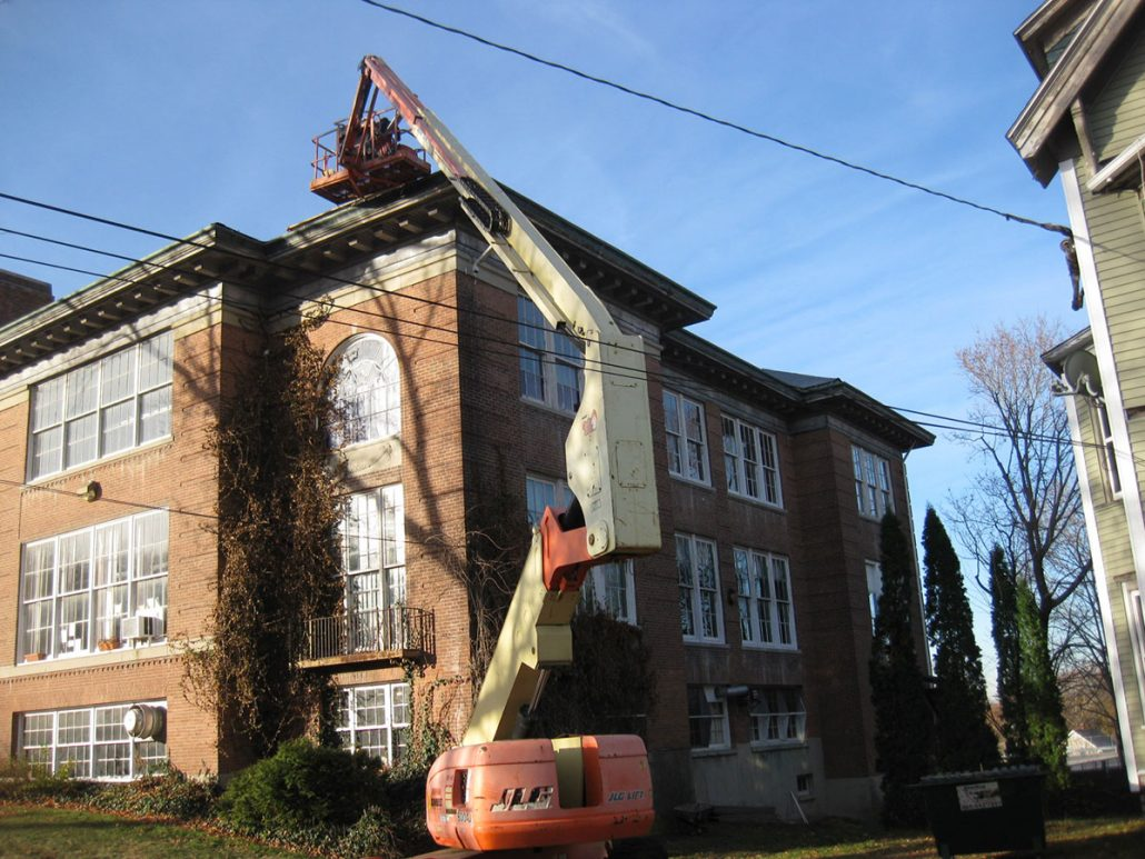 Using a crane to install new roof on historic building