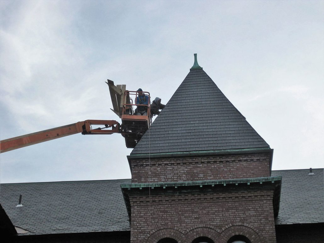 Installing new roof on tower of old building