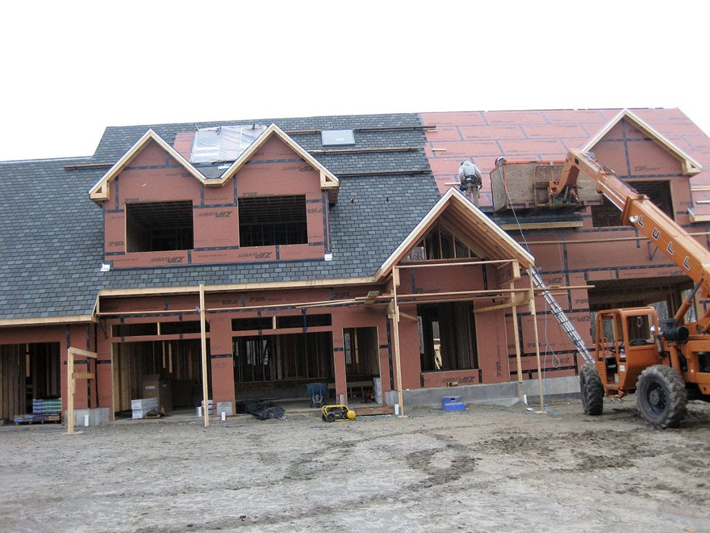 Roof shingles being installed during new home construction