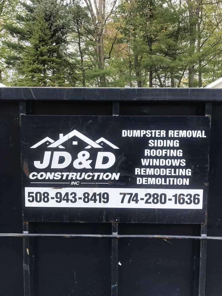 Dumpster with JD&D Construction sign on the side