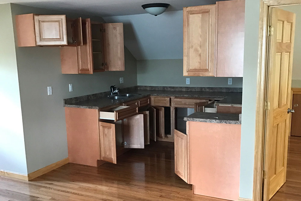 Newly renovated kitchen with blond cabinetry and polished hardwood floors